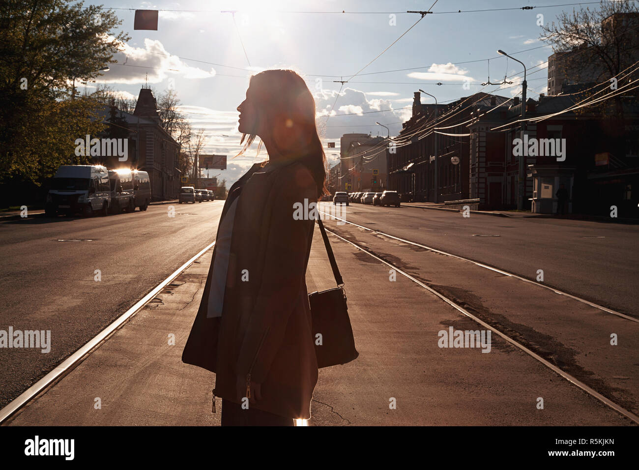 Urban girl standing out from the crowd at a city street - Stock Image