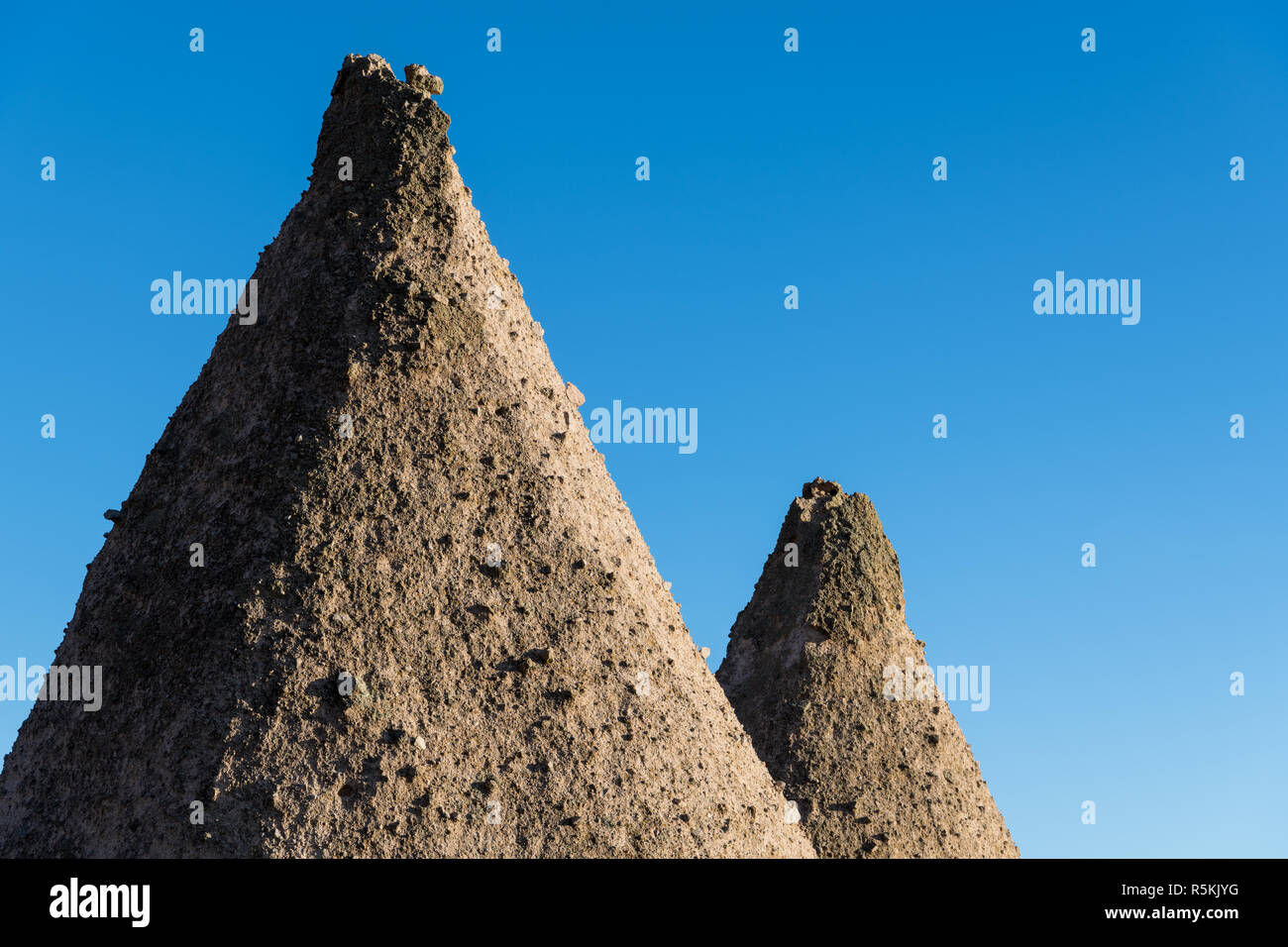 The sharp peaks of two roughly textured rock formations against a perfect blue sky at Kasha-Katuwe Tent Rocks National Monument, New Mexico - Stock Image