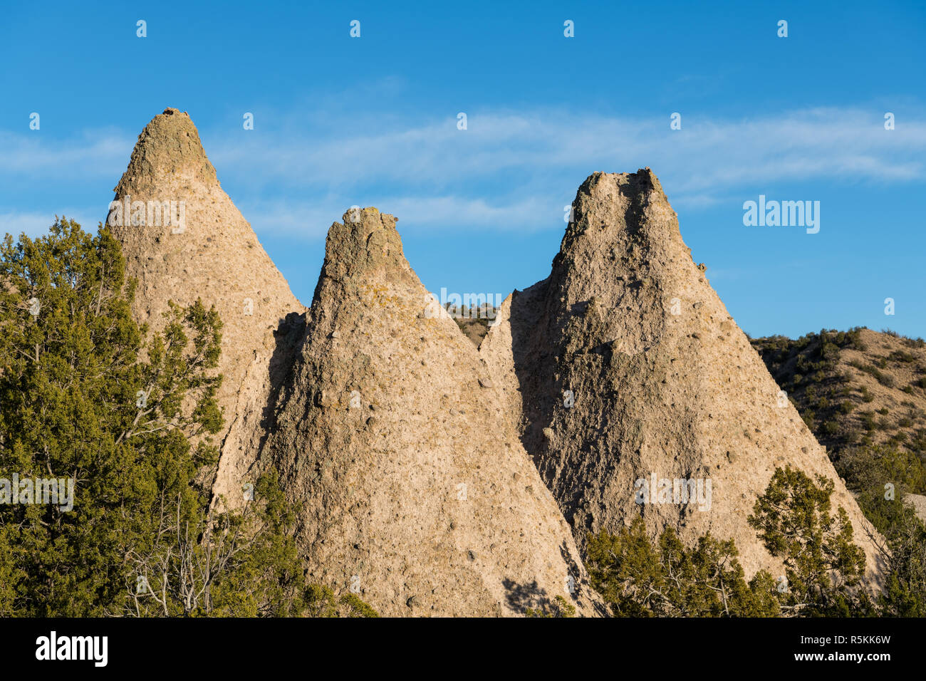 A group of three sharply pointed, cone-shaped rock formations at Kasha-Katuwe Tent Rocks National Monument, New Mexico - Stock Image