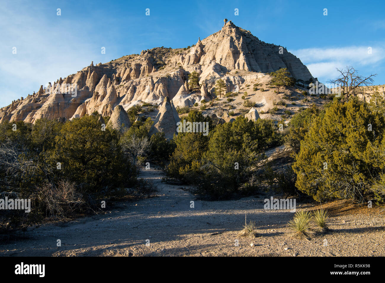 A high, steep desert peak with unusual towers and rock formations in the light of sunset at Kasha-Katuwe Tent Rocks National Monument, New Mexico - Stock Image