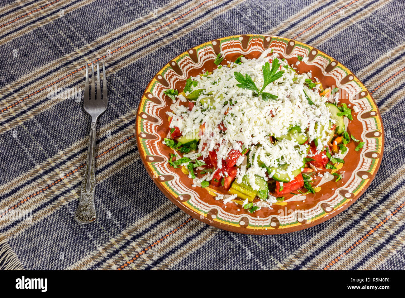 Traditional bulgarian Shopska salad on a table spread. Made by classic recepie. - Stock Image