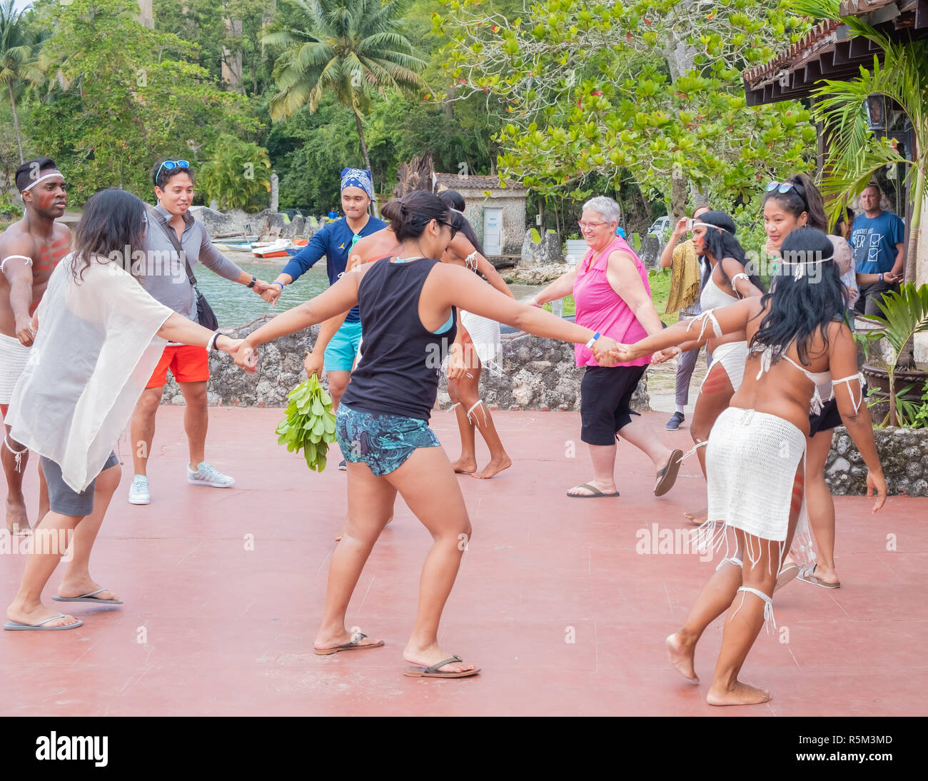 Tourists dance with a group of indigenous people near Matanzas Cuba. - Stock Image
