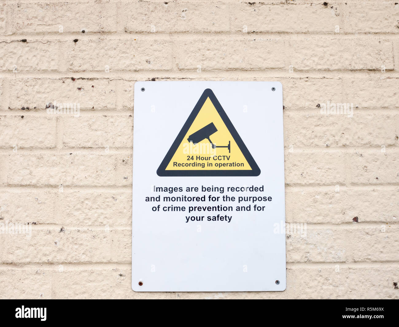 a white placard sign on wall surveillance cctv warning - Stock Image