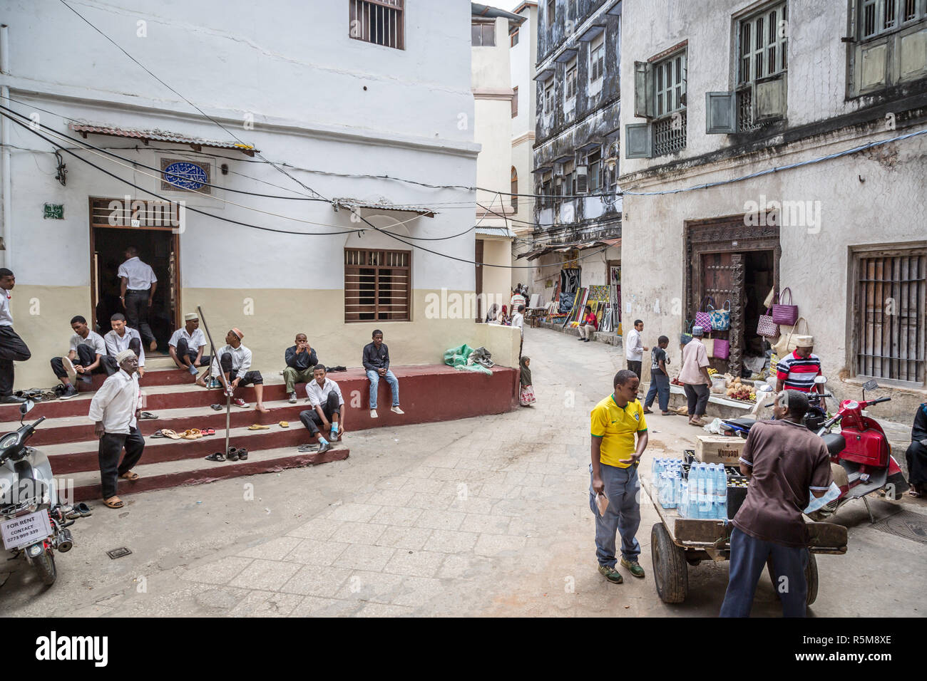 STONE TOWN, ZANZIBAR - AUGUST 15, 2015: Local people on a typical alley street in Stone Town. Stone Town is the old part of Zanzibar City, the capital - Stock Image