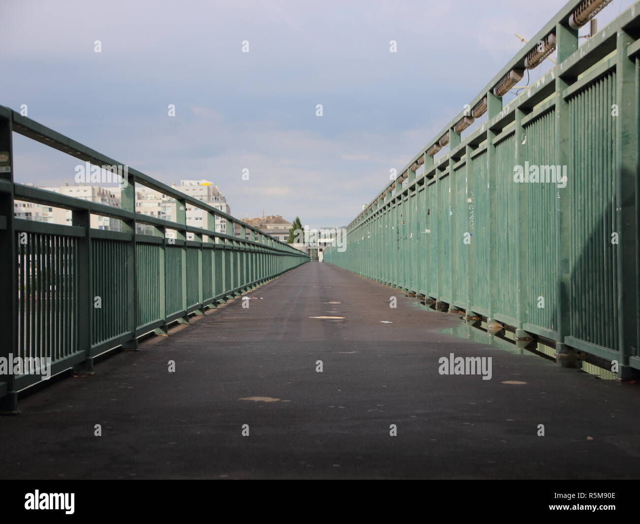 Long Asphalt Footpath with Green Metal Banisters Perspective Stock Photo