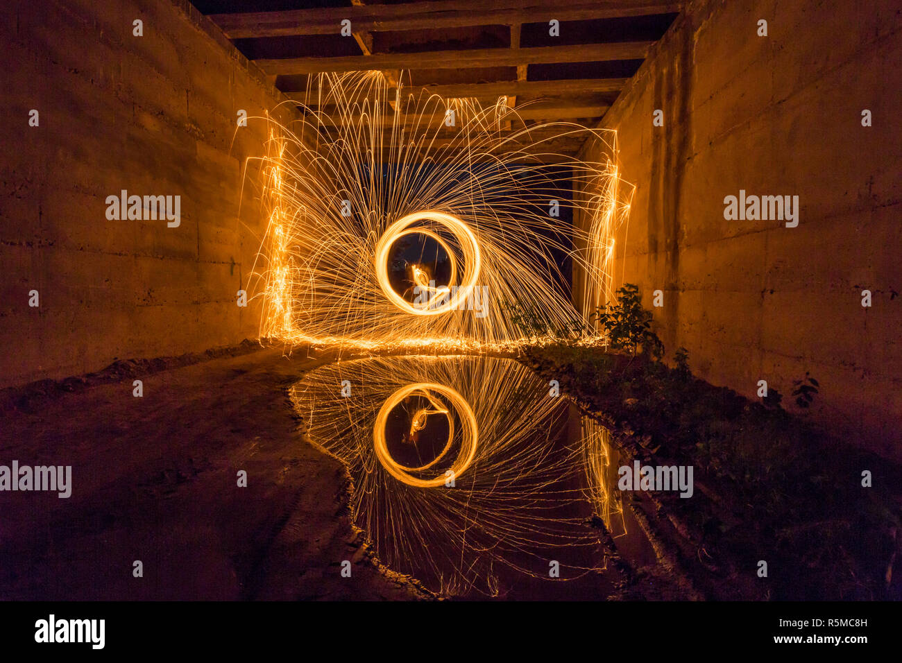 Steel wool spinning reflected in the water under a bridge Stock Photo