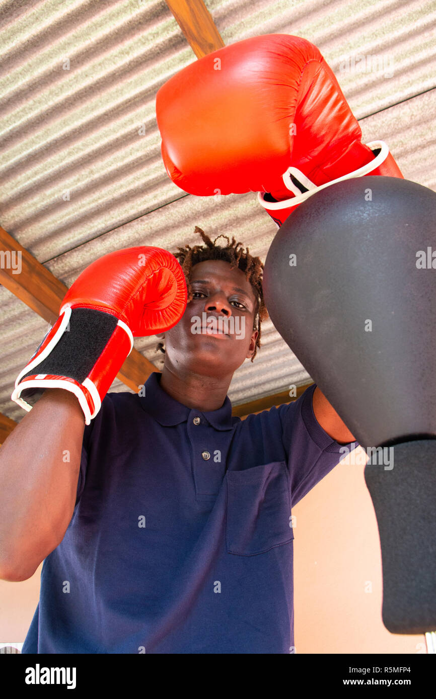 Attractive young black man very handsome practicing boxing - Stock Image