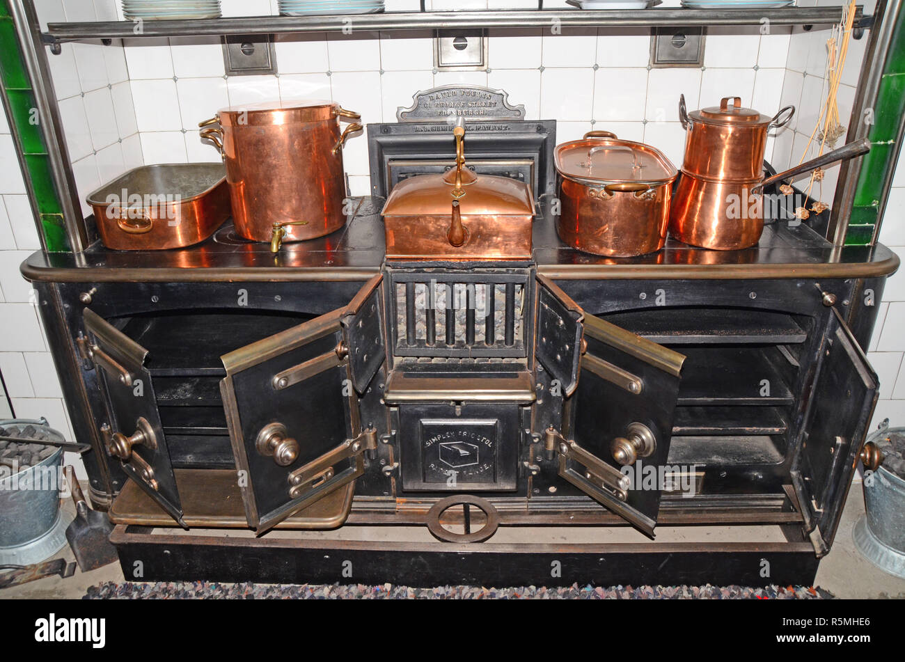 large. antique / vintage kitchen hearth with a variety of  copper pans and pots on it. - Stock Image