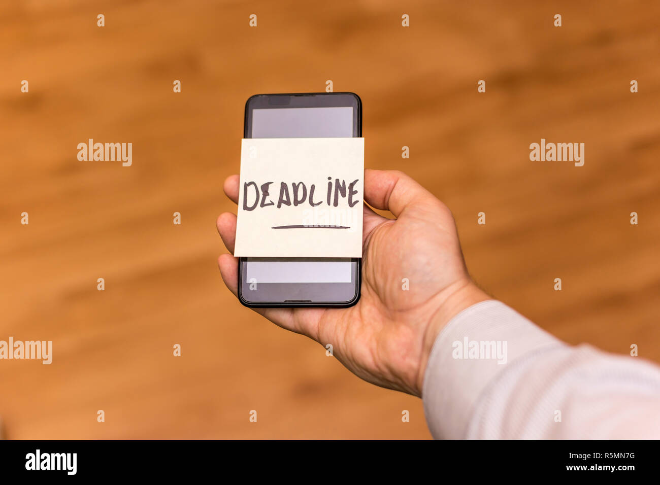 Human hand holding a smartphone with yellow note sticked on it. The word deadliner is written on the note. - Stock Image