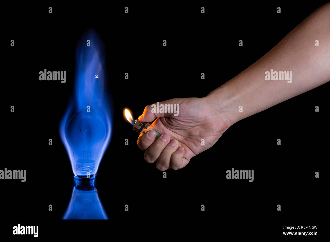 Hand lighting a lightbulb isolated on black background. Wrong usage concept. - Stock Image