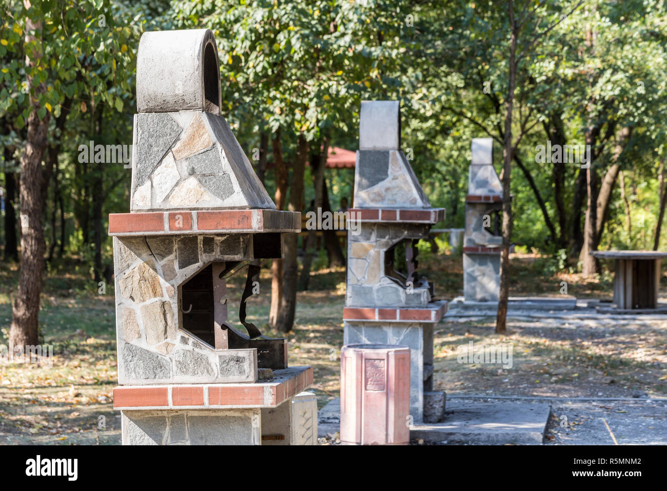 Three barbeque fireplaces located in a park for public usage. - Stock Image