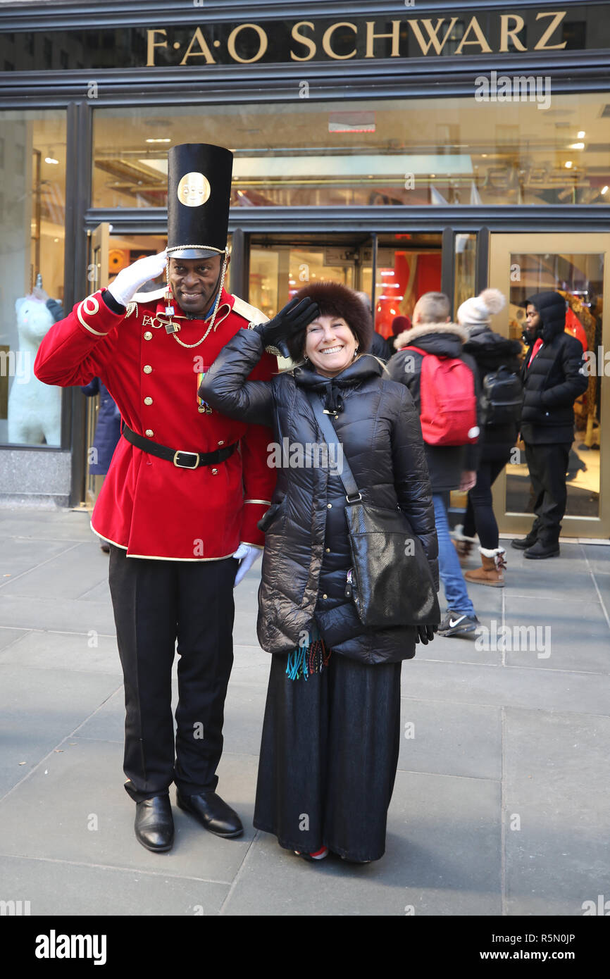 A doorman dressed as a toy soldier stands outside newly reopened the FAO Schwarz flagship store at Rockefeller Plaza in Midtown Manhattan - Stock Image