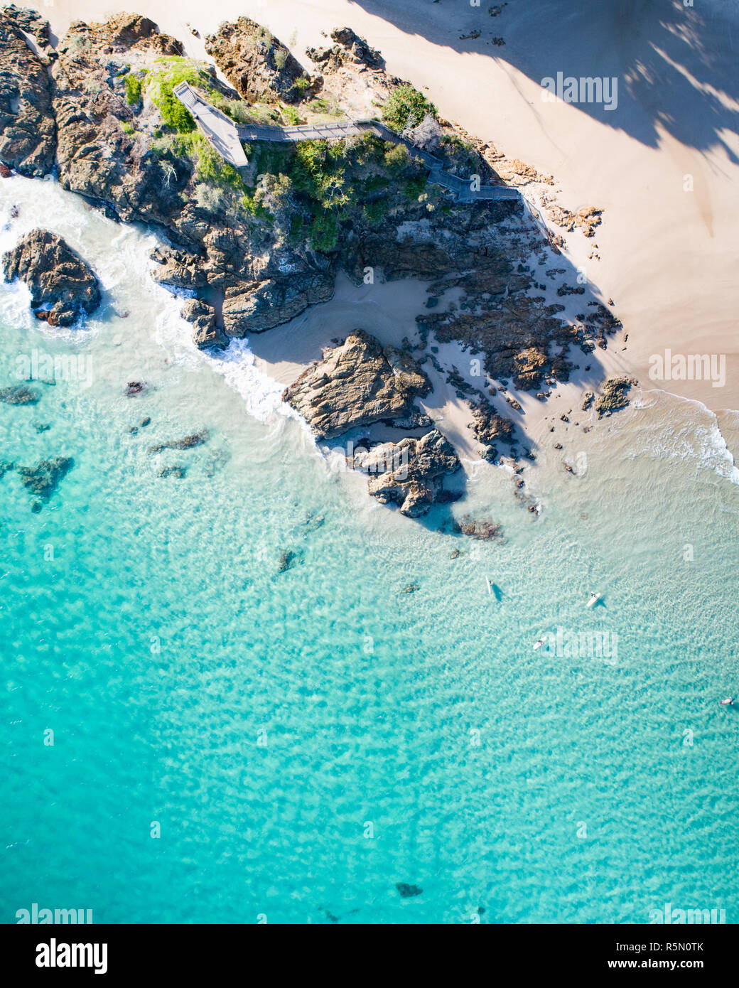 Aerial view above rock and the ocean. Beautiful blue turquoise water, swimmer and white sand view from above. - Stock Image