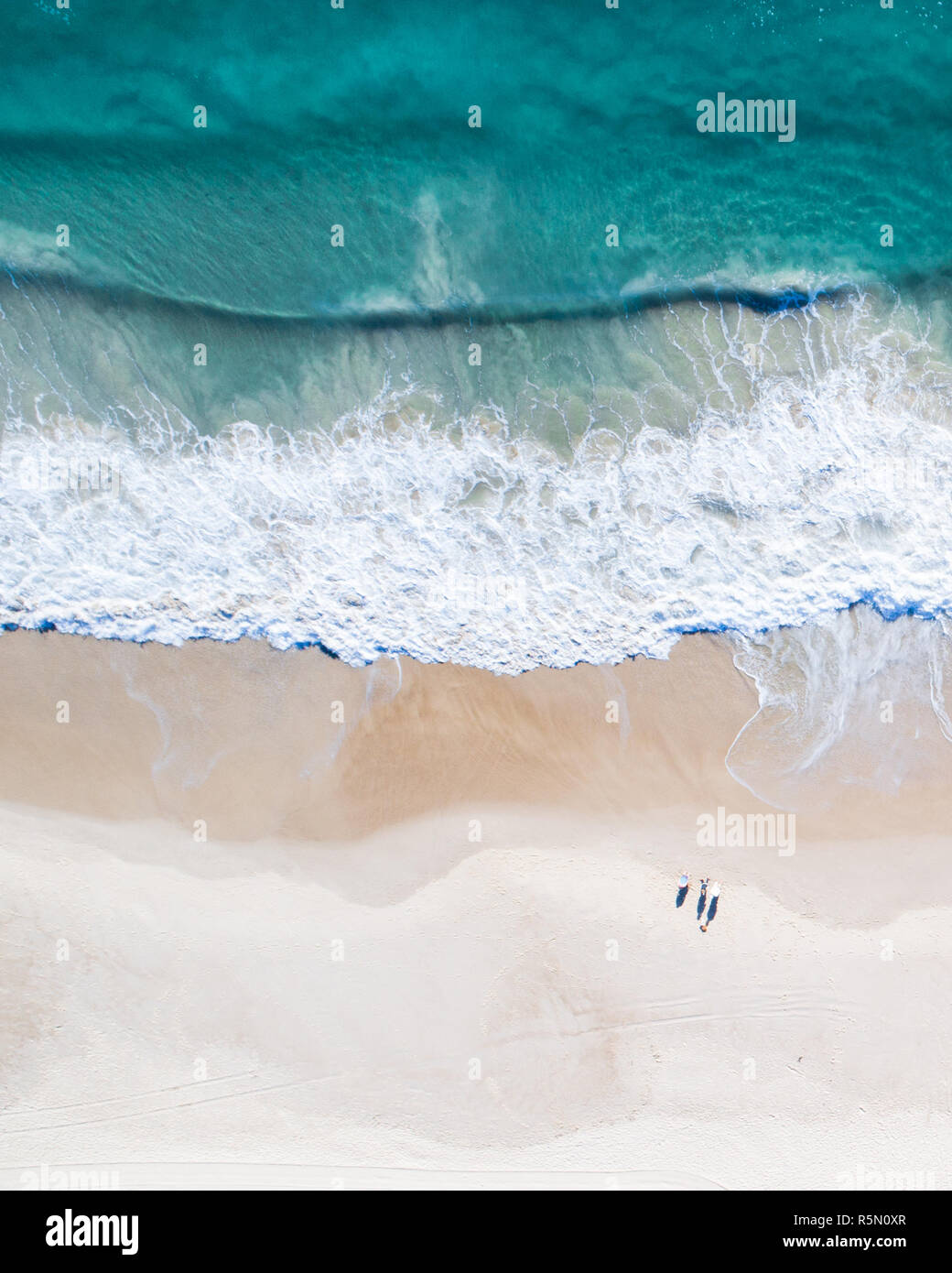 Beautiful blue wave crashing on white sand. Amazing aerial view of a beach in Australia - Stock Image