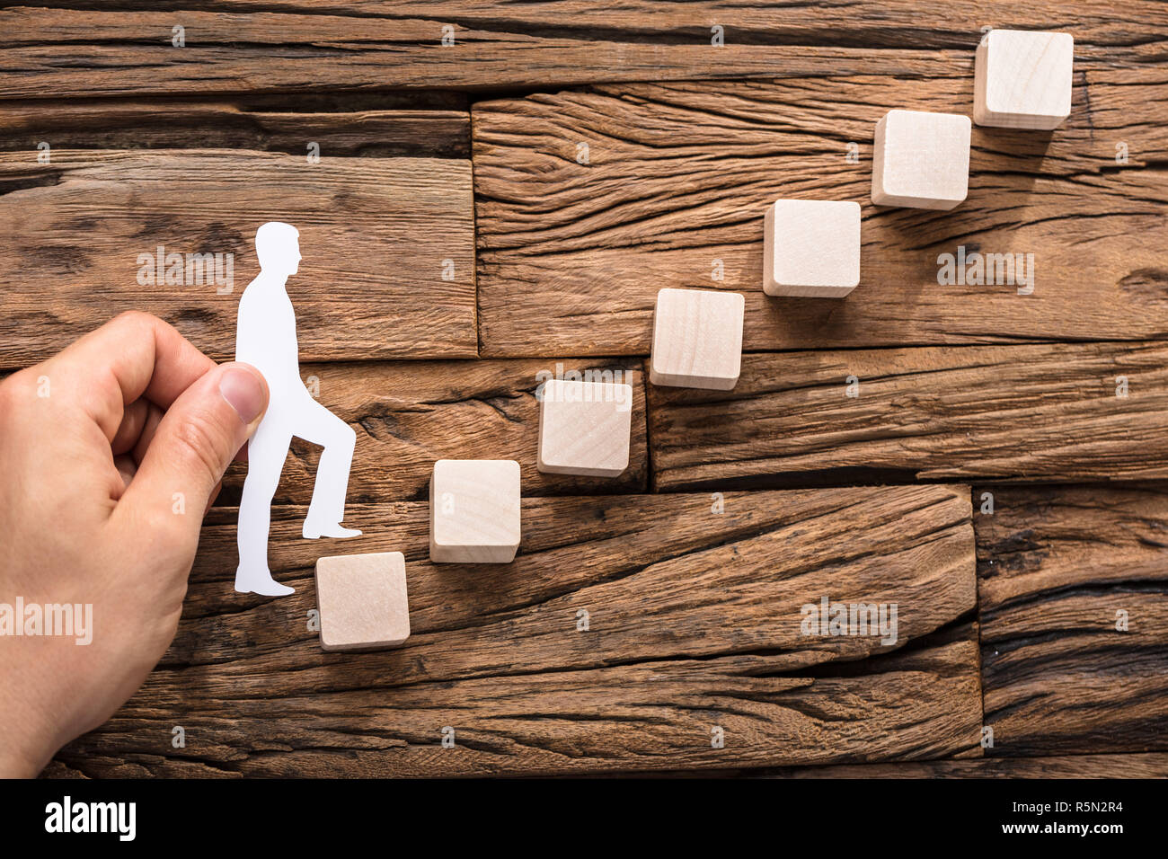 Hand Stepping The Paper Cut Out Figure On Increasing Block - Stock Image