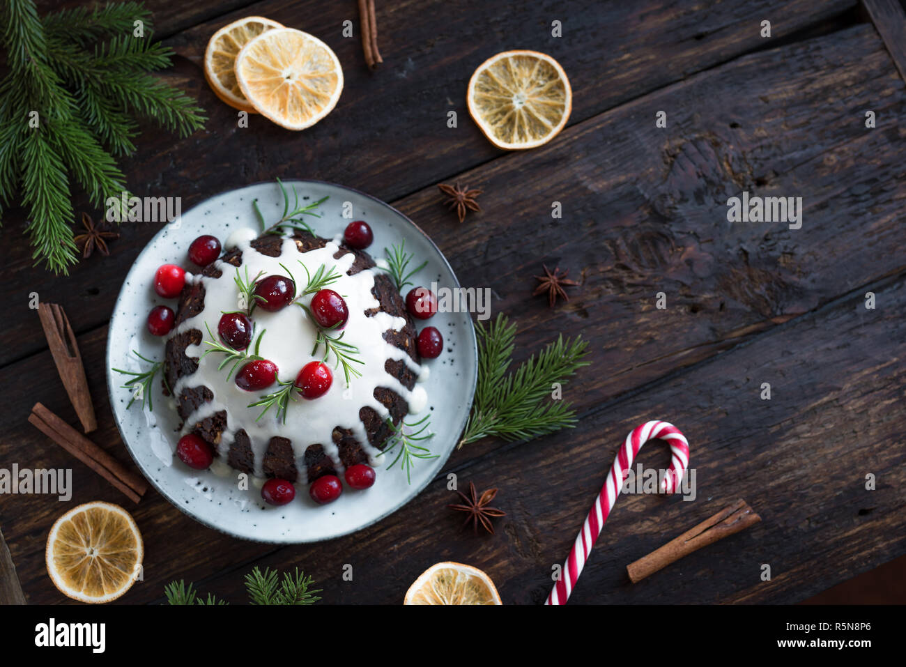 Christmas Pudding, Fruit Cake decorated with icing and cranberries on rustic wooden table, copy space, top view. Homemade traditional christmas desser - Stock Image