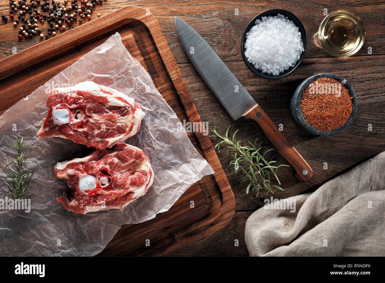 Raw lamb neck meat on white cooking paper and wooden cutting board. Decorated with herbs, spices, chef's knife and napkin. Overhead view. - Stock Image