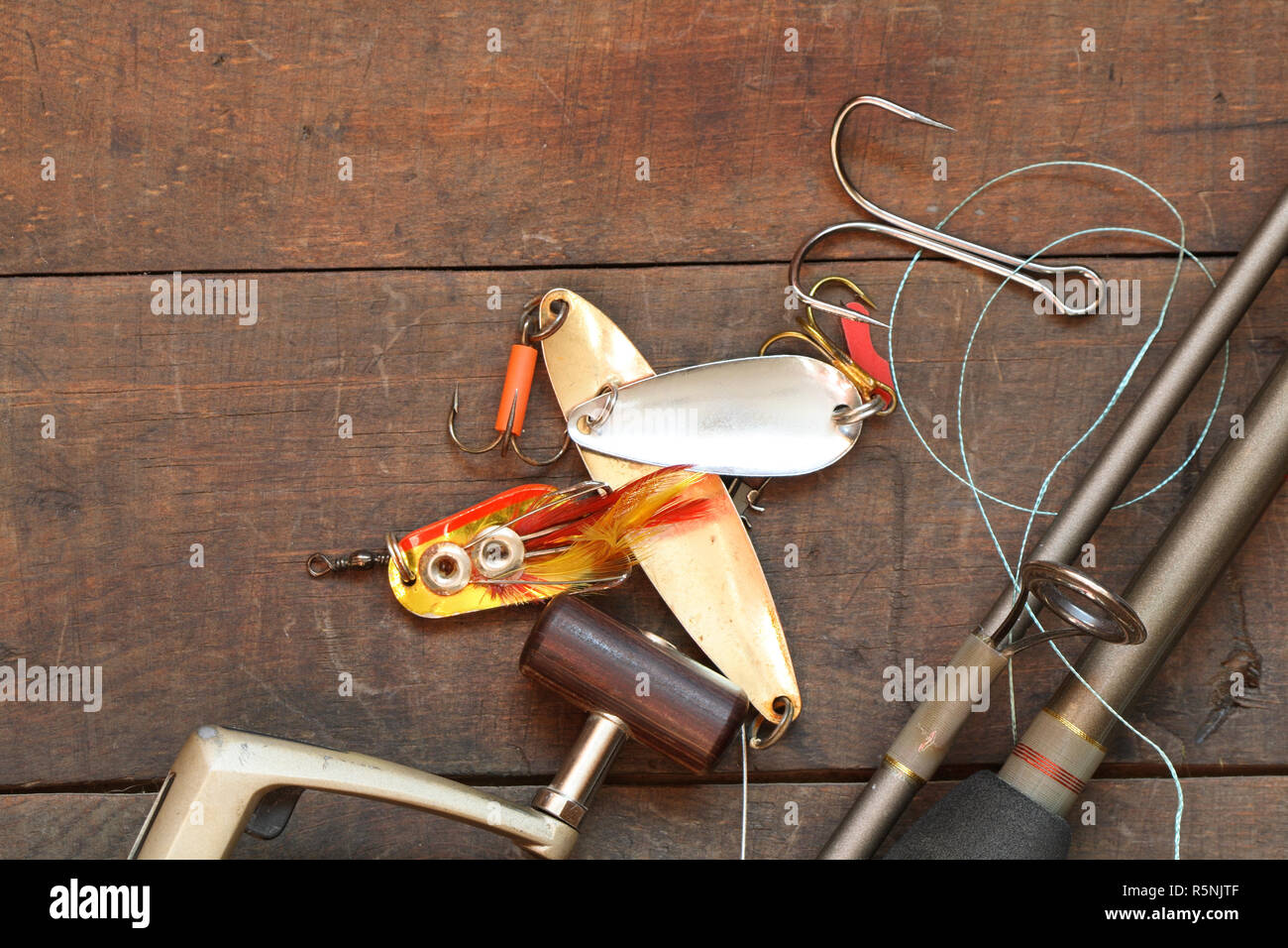 Closeup of spinning rod and other fishing tacle lying on wooden background Stock Photo