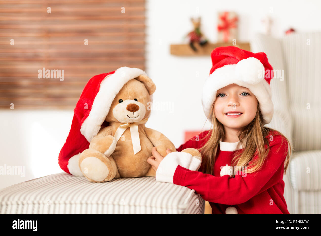 9ff3688ee Cute young girl wearing santa hat holding her christmas present, soft toy  teddy bear. Happy kid with xmas present, smiling and looking at camera.