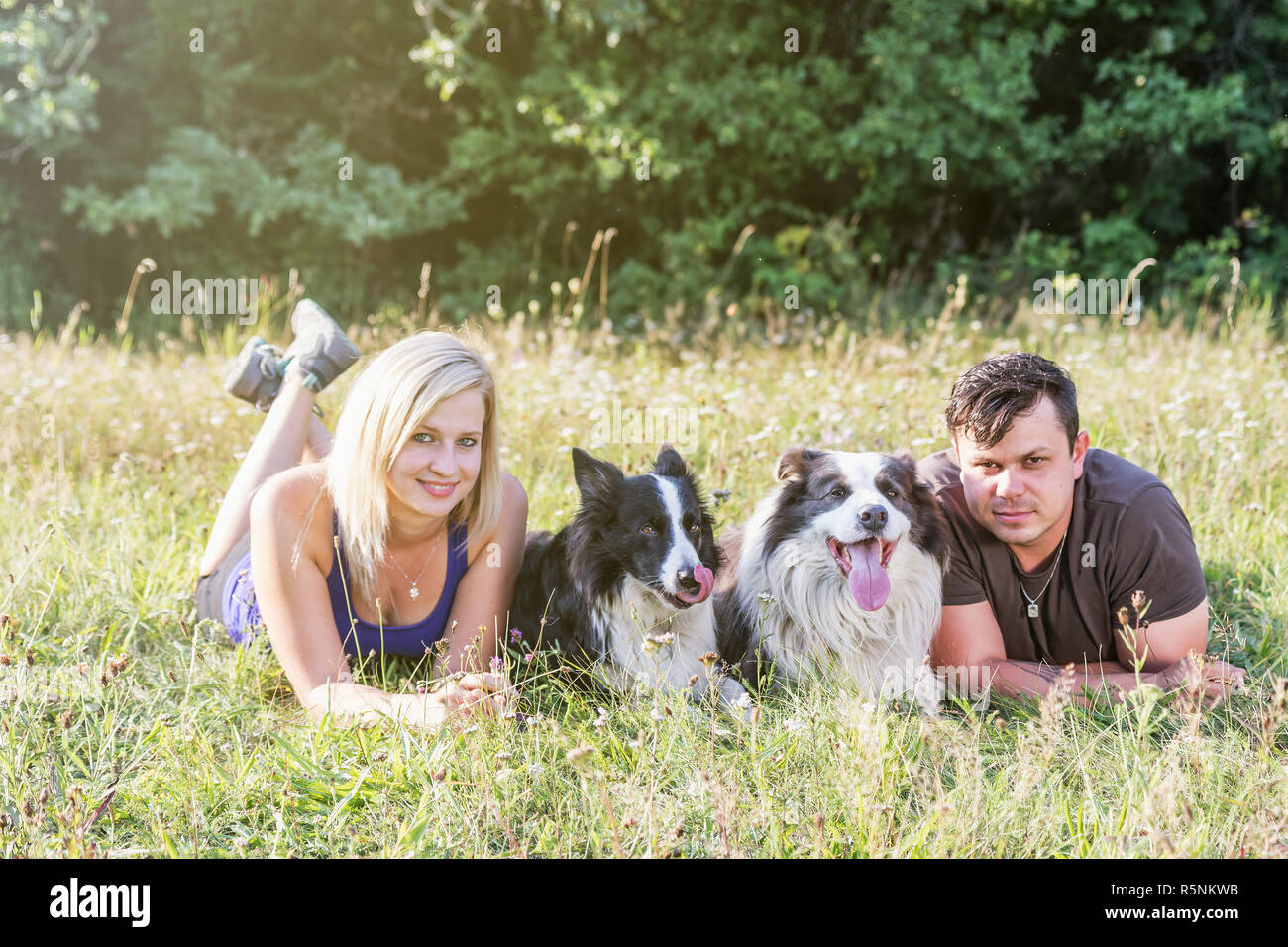 Young man and woman are lying in grass with a pair of dogs - Stock Image