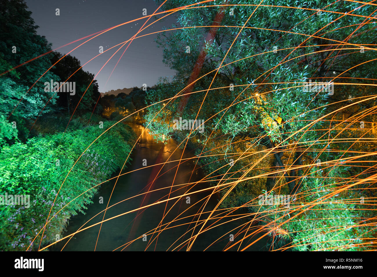 illuminated river with sparks and fire during the summer - Stock Image