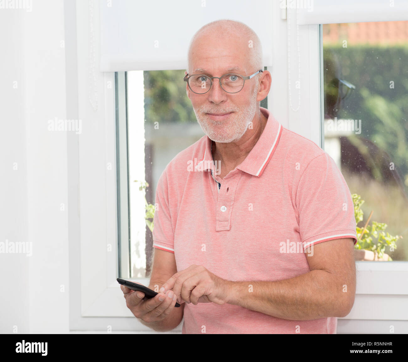 Mature man with eyeglasses typing message on smartphone Stock Photo