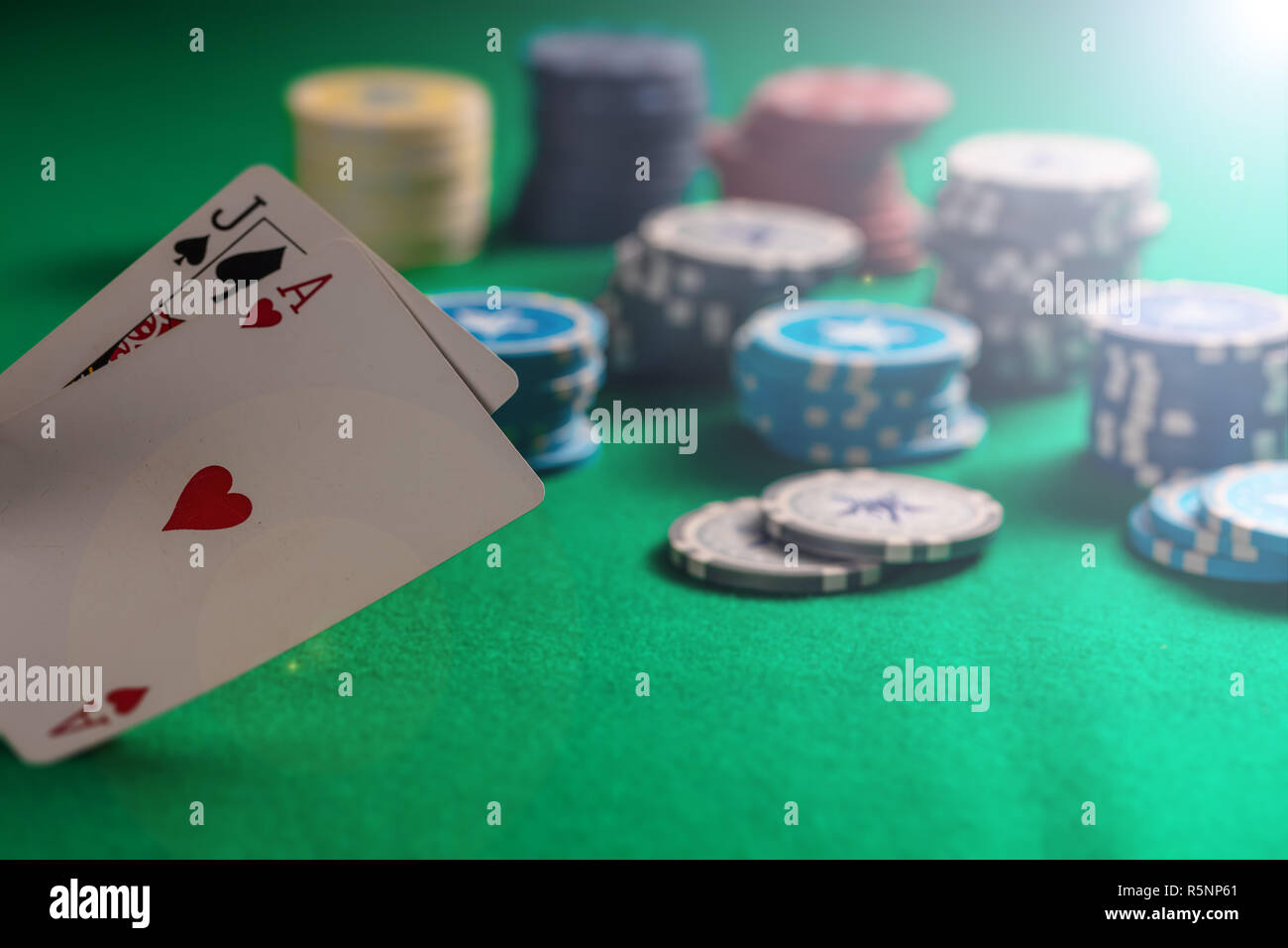 Casino, gambling concept. Blackjack and poker chips on green felt background - Stock Image