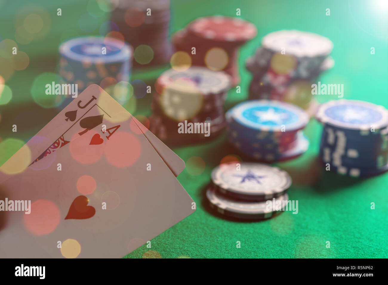 Casino, gambling concept. Blackjack and poker chips on green felt bokeh background - Stock Image
