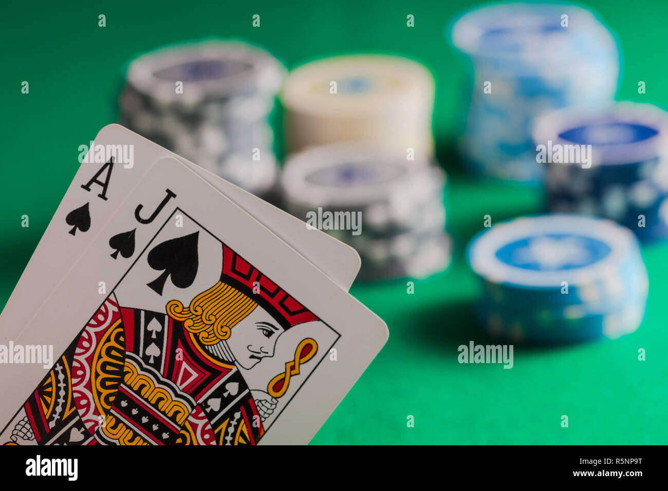 Casino, gambling concept. Blackjack and poker chips on green felt blur background - Stock Image