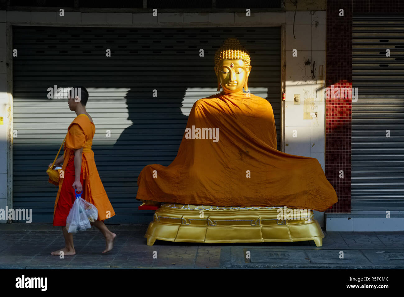 A novice monk passed a Buddha statue placed in front of a shop for religious artifacts, in Bamrung Muang Road, Bangkok, Thailand - Stock Image