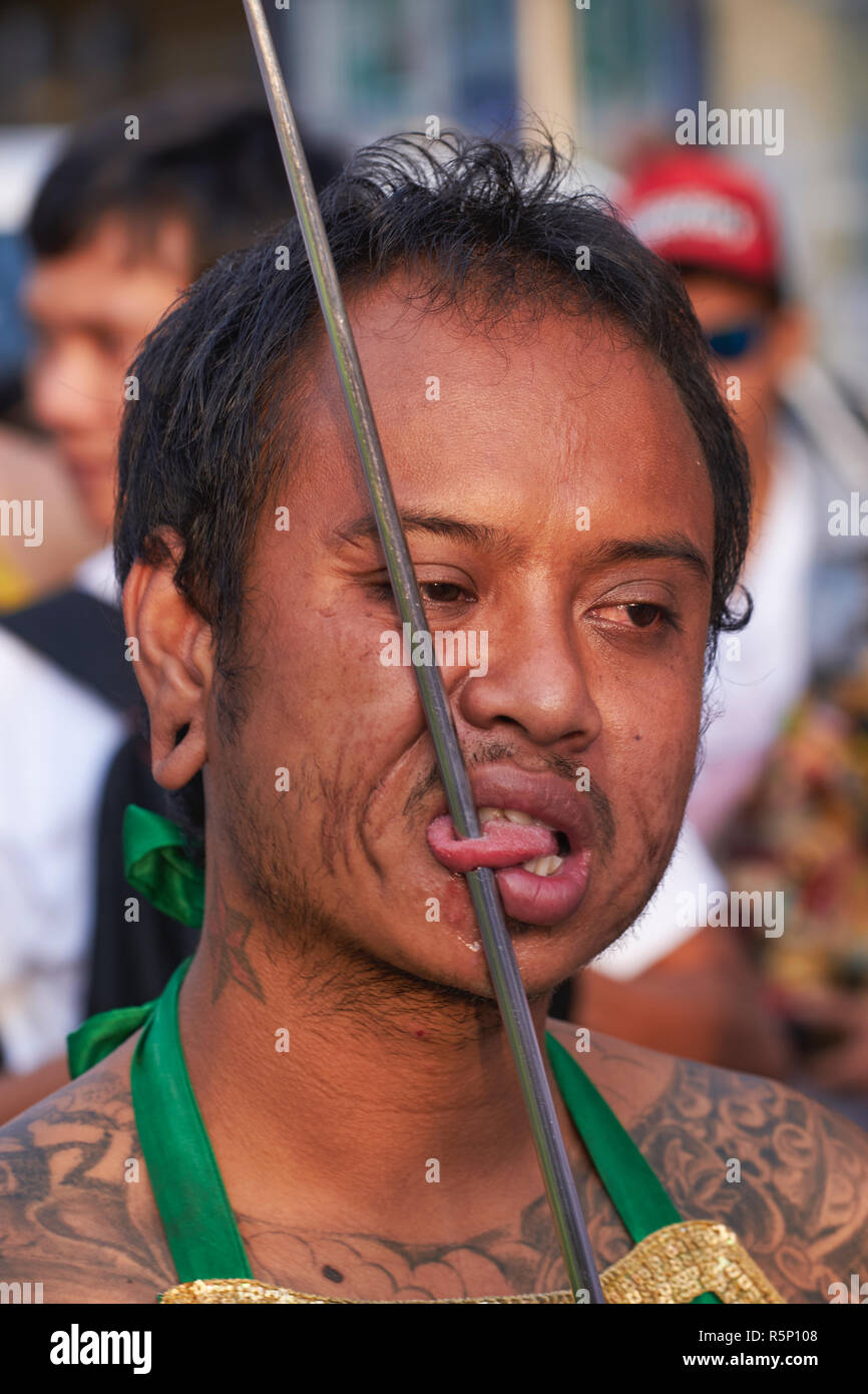 A spirit medium with his tongue pierced as part of the rituals for the Vegetarian Festival in Phuket, Thailand, in a procession through Phuket Town - Stock Image