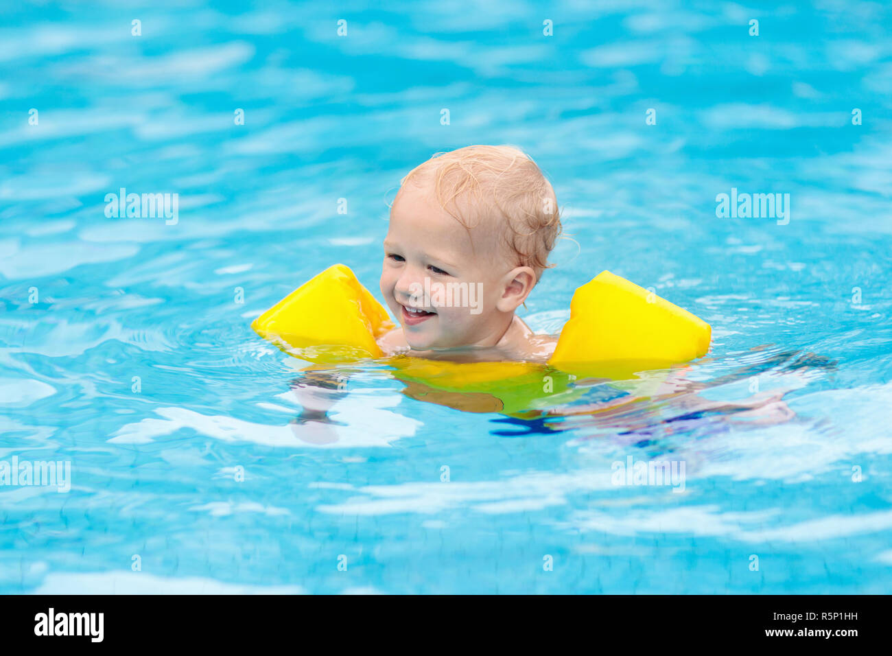 6792a3dc33 Baby with inflatable armbands in swimming pool. Little boy learning to swim  in outdoor pool