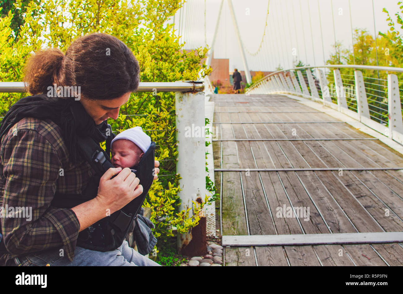 newborn father together park baby carrier fatherhood background - Stock Image