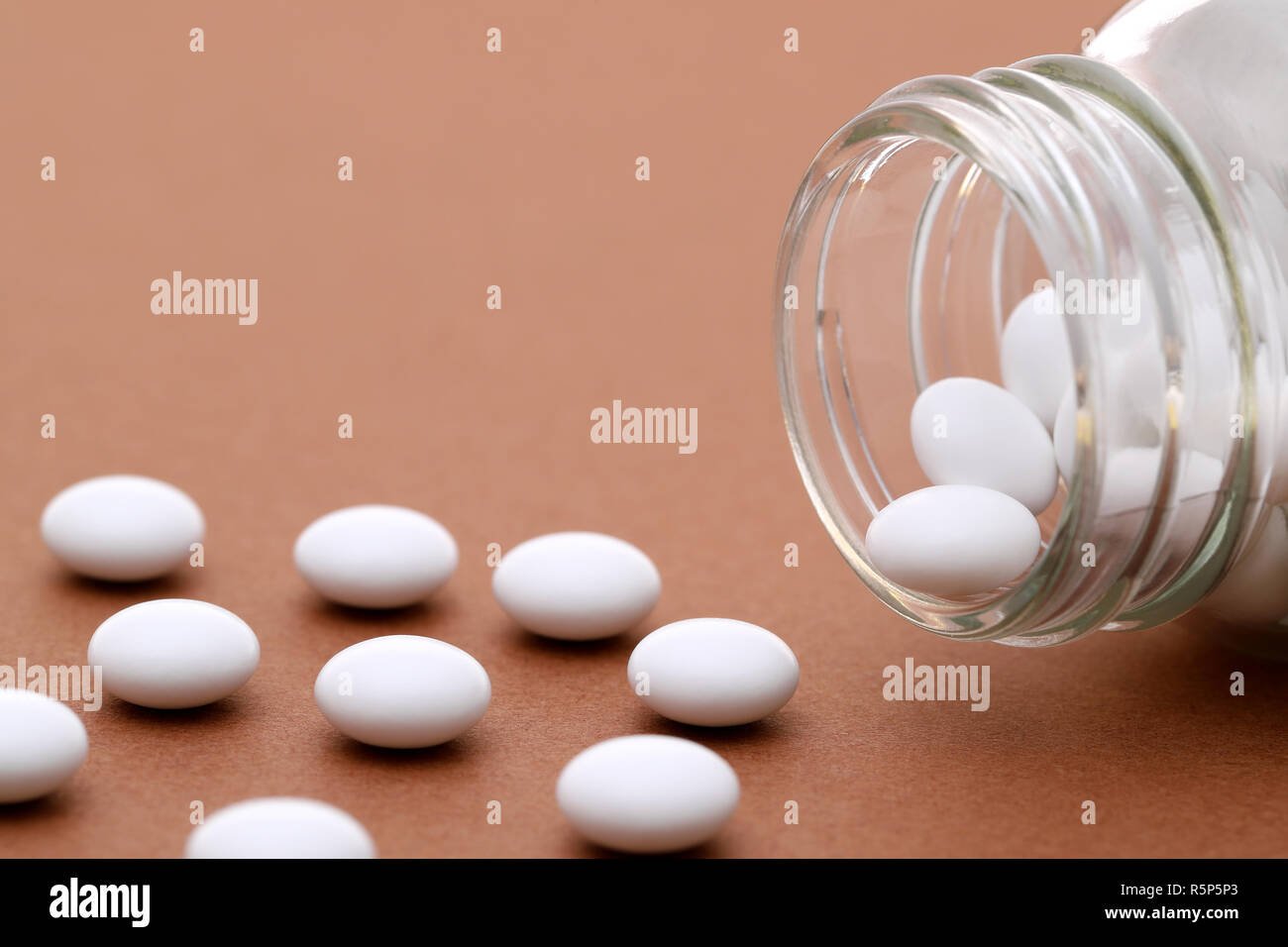 Glass bottle and pills on light brown background Stock Photo