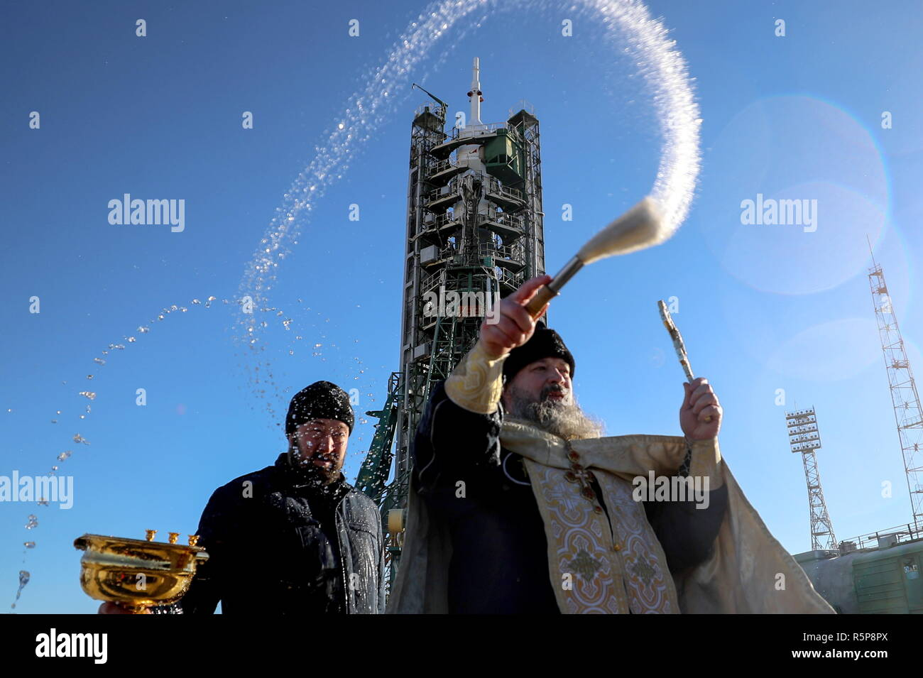 Kazakhstan. 02nd Dec, 2018. KAZAKHSTAN - DECEMBER 2, 2018: Russian Orthodox clergy sprinklas blessed water during the blessing of a Soyuz-FG rocket booster carrying the Soyuz MS-11 spacecraft at Baikonur Cosmodrome; the launch of the Soyuz MS-11 spacecraft is scheduled for December 3, 2018, 14:31 Moscow time. Sergei Savostyanov/TASS Credit: ITAR-TASS News Agency/Alamy Live News - Stock Image