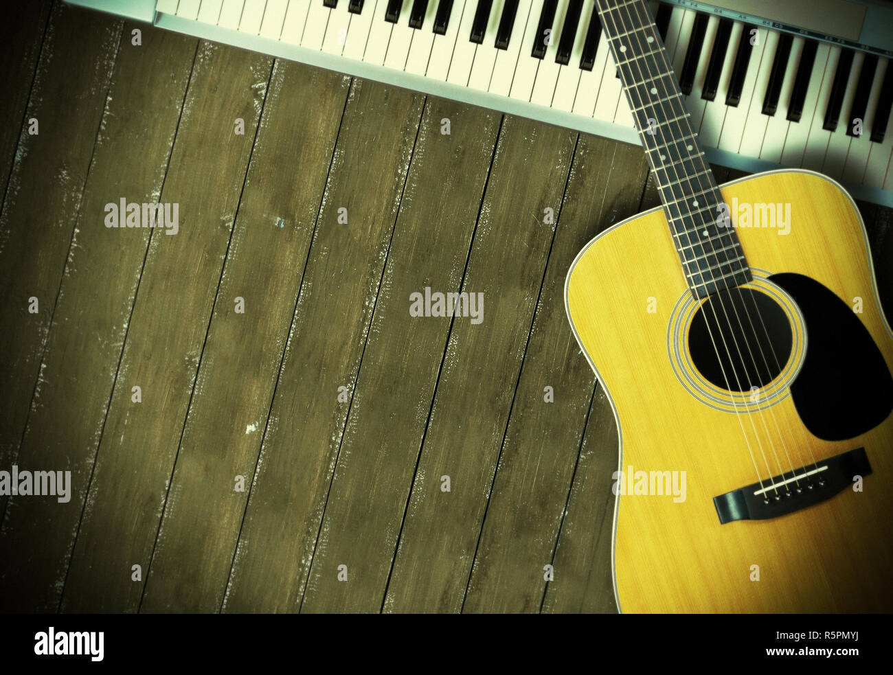 Musical instrument - Sloseup MIDI piano 61 key keyboard and acoustic guitar on a wooden background - Stock Image