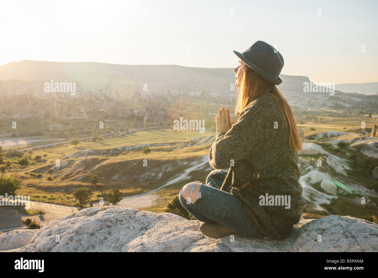 A girl practices yoga or meditation or searching for a soul. Solitude and unplugged - Stock Image