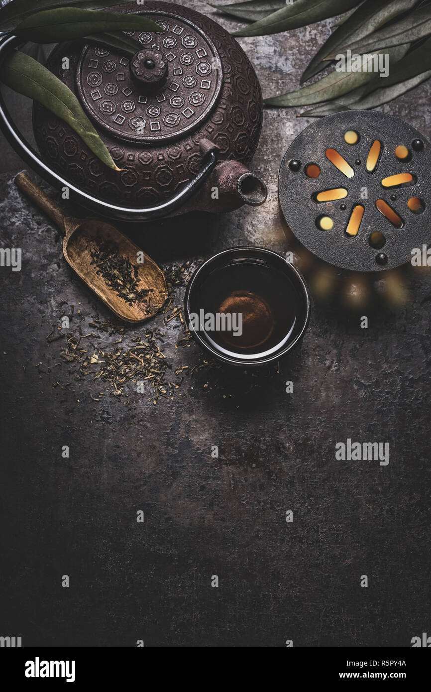 Black iron asian tea set on dark rustic background with teapot and fresh tea  leaves, top view with copy space for your design. Authentic vintage style