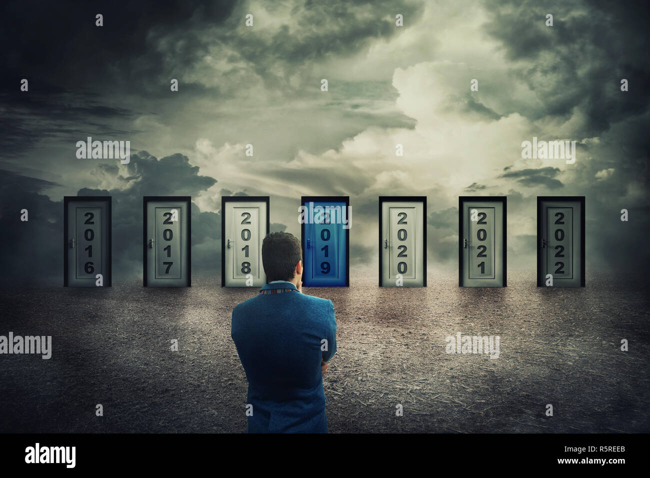 Rear view man in front of many doors with different years numbers. Difficult decision, concept of the important choice in life, select to live the pre - Stock Image