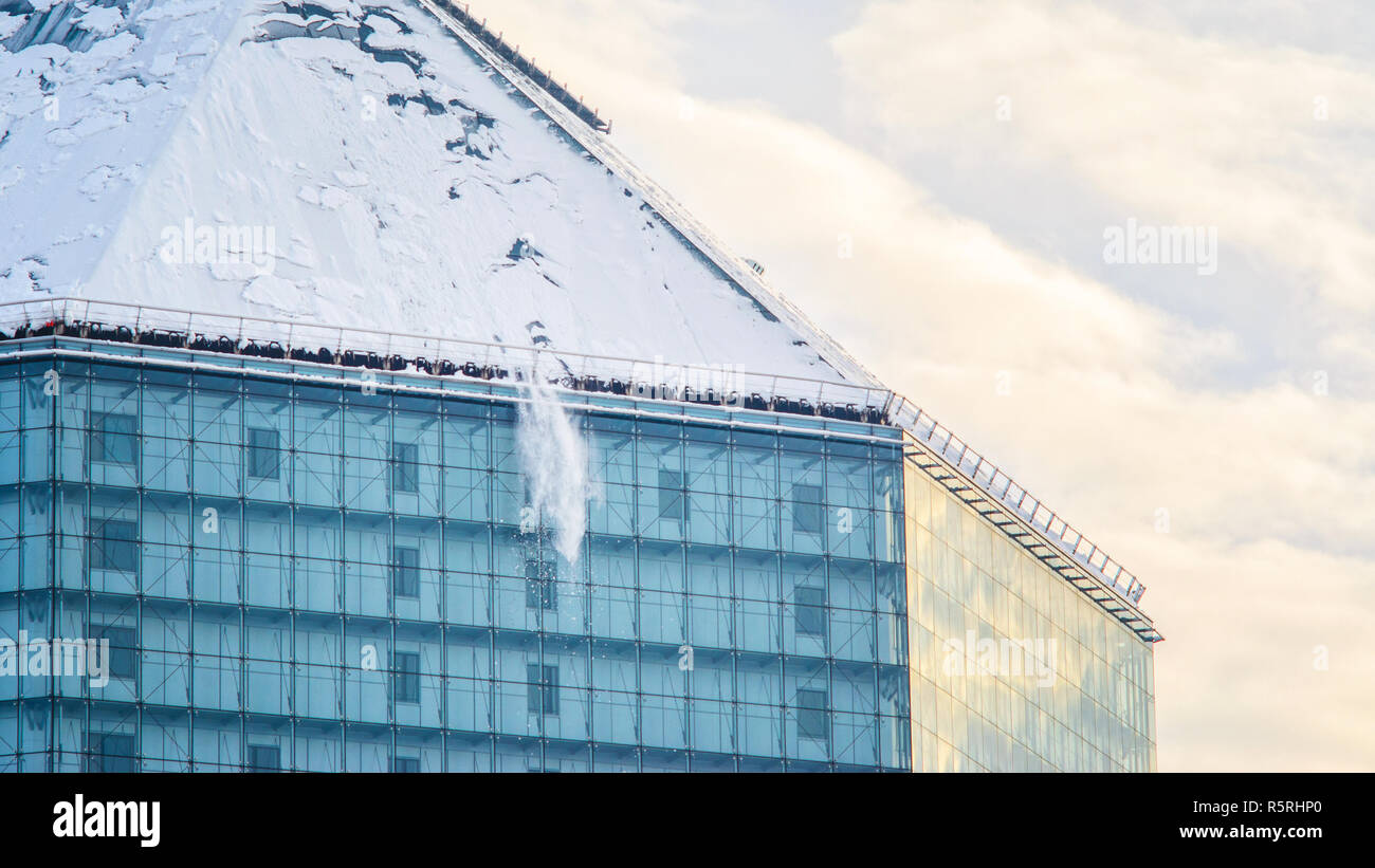 Snow fall from the roof. Sloping glass facade wall winter problems - Stock Image