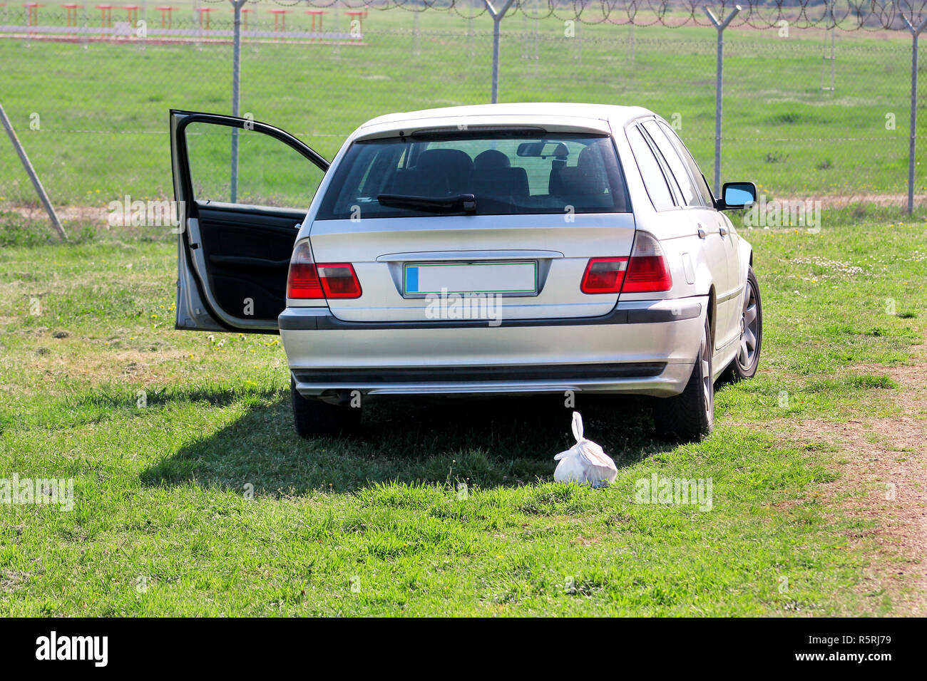 Bag of garbage on grass left behind by car. Nature is destroyed. Trash left in natural environment as an example of environmental pollution. Recycling - Stock Image