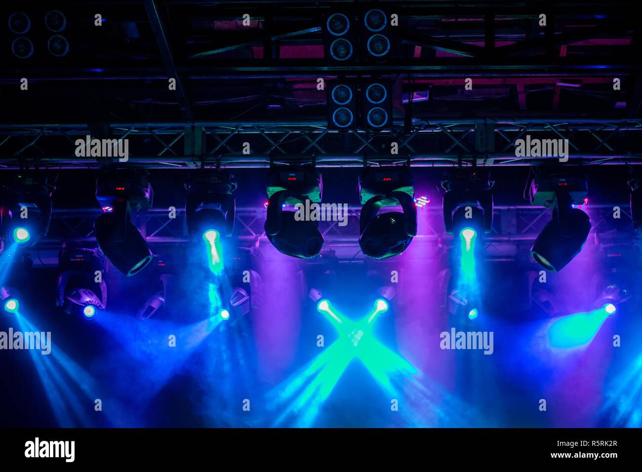Stage, concert light. Modern spotlights equipment. Beautiful multicolored rays shine through the smoke. - Stock Image