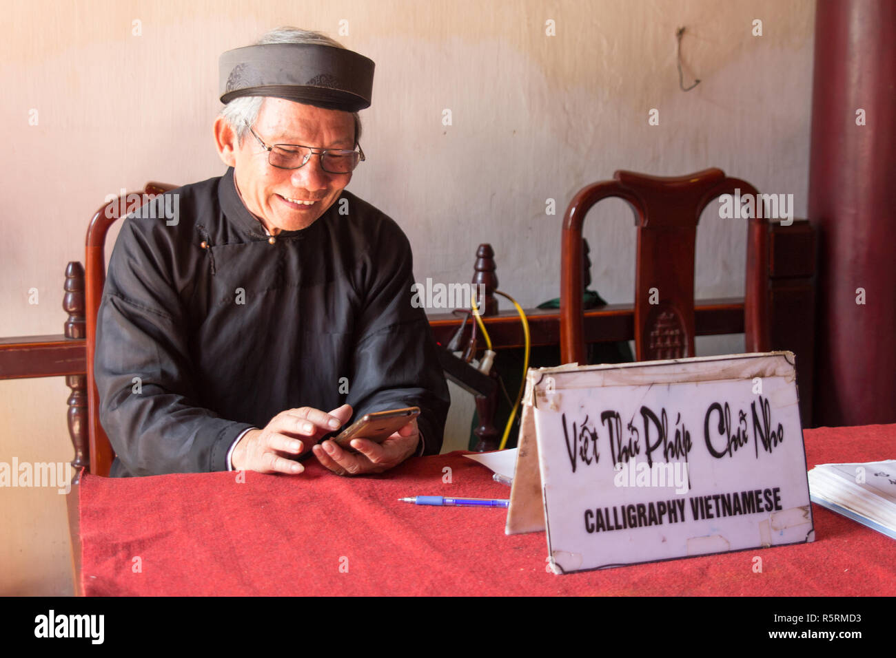 Hanoi, Vietnam - CIRCA October 2015: calligrapher in Hanoi, Vietnam offers his services and uses mobile phone at the same time. - Stock Image