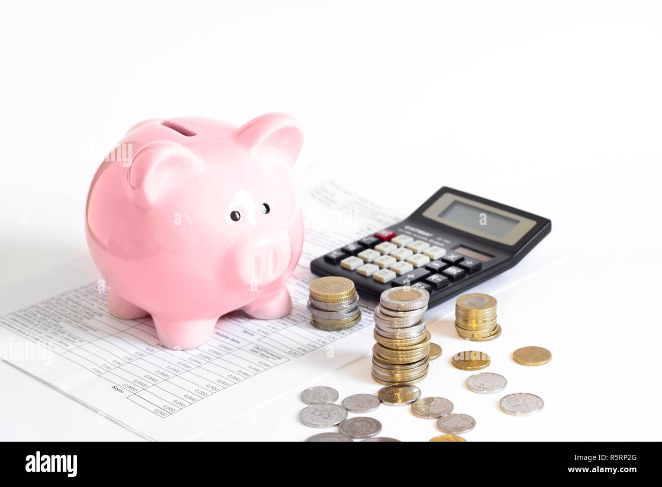 piggy bank with coins and calculator Stock Photo