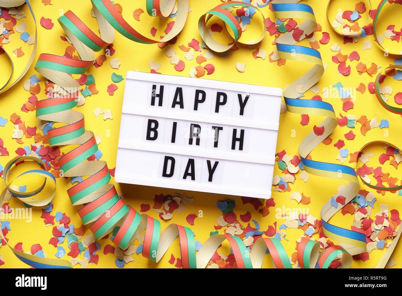 happy birthday party celebration flat lay with confetti and streamers on yellow background - Stock Image