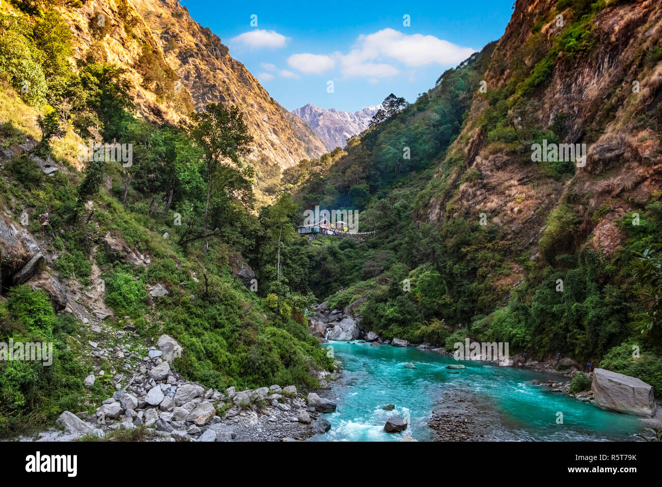 Langtang river in Nepal with human settlement in the background - Stock Image