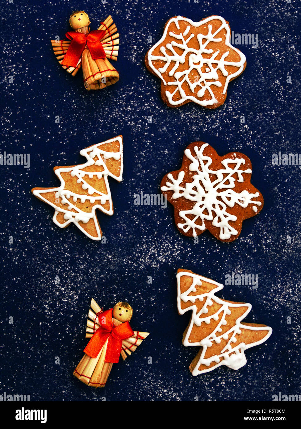 Christmas cookies Top view photo Classic gingerbreads in shapes of house, spruces and snowflakes with icing are lying on dark blue desk - Stock Image