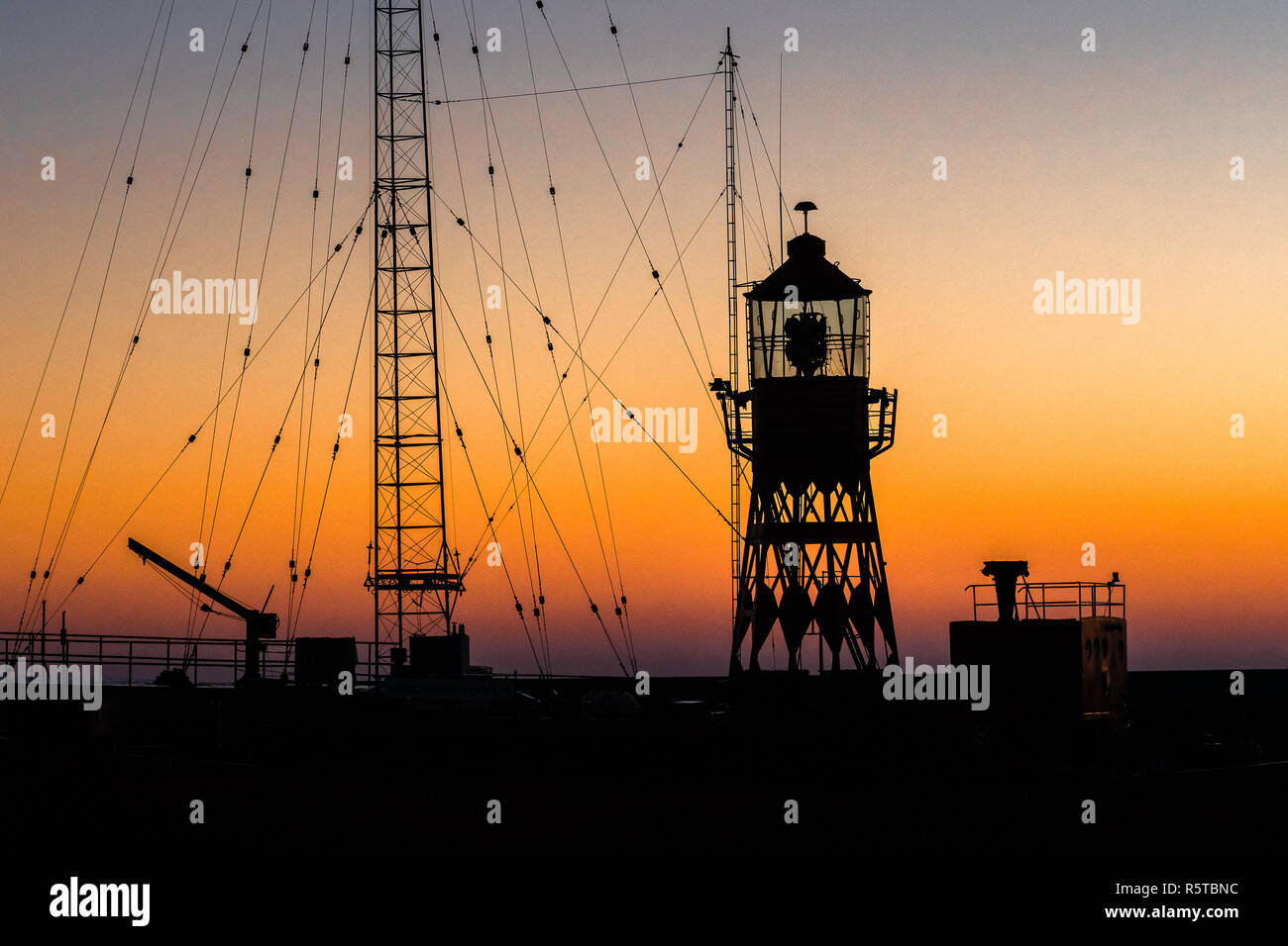 Abstract photo with industrial character of a lighthouse against a brightly colored sky with beautiful intense colors of the sunset. Minimalitic image - Stock Image