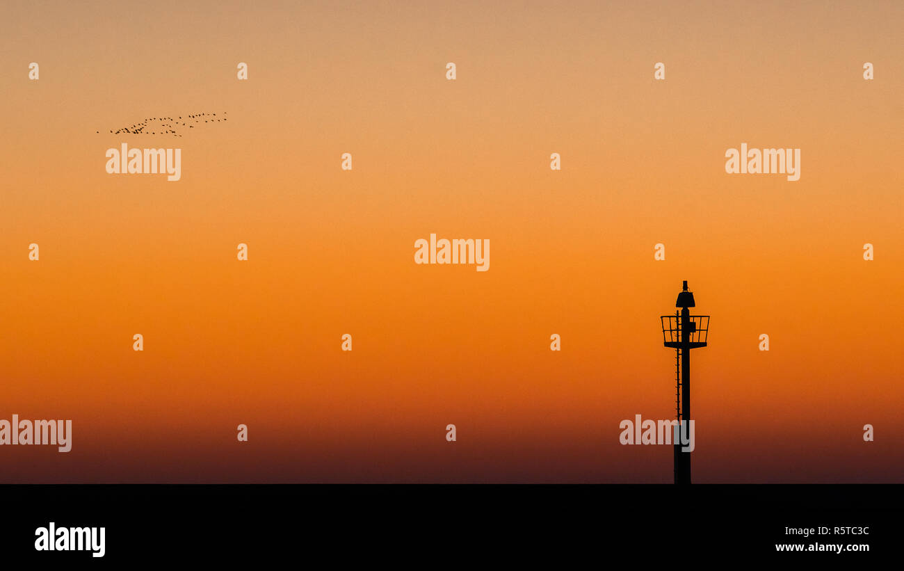 Abstract photo of a light signal or light buoy against a brightly colored sky with beautiful intense colors of the sunset. Minimalitic image with cont - Stock Image