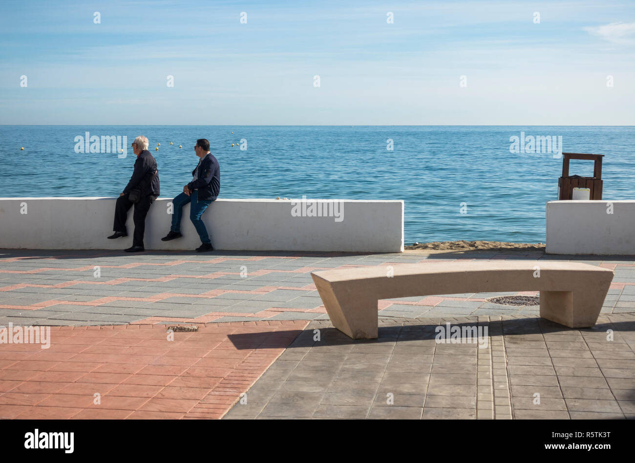 Two older men sitting at beach front promenade , with modern public bench in front, La Cala, Andalusia, Spain. - Stock Image